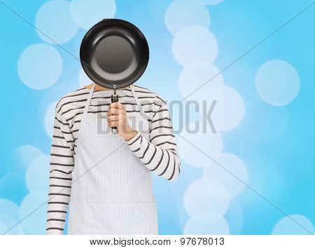 people, cooking, culinary and identity concept - man or cook in apron hiding his face behind frying pan over blue lights background