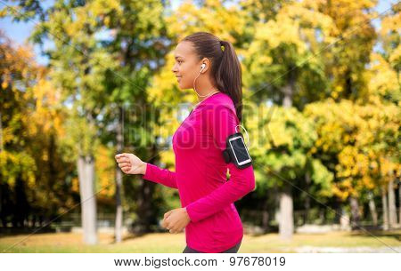 sport, fitness, technology and people concept - smiling young african american woman running with smartphone and earphones over autumn park background