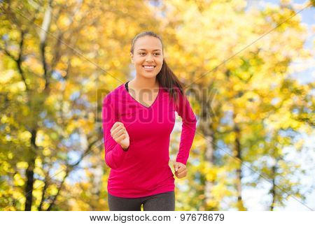 fitness, sport, training and people concept - smiling african american woman running outdoors over autumn trees background