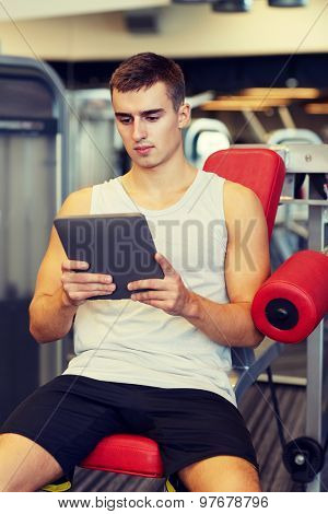 sport, bodybuilding, lifestyle, technology and people concept - young man with tablet pc computer in gym