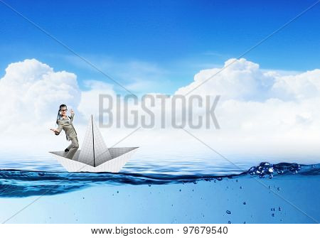 Businessman escapes from the crisis on a paper boat