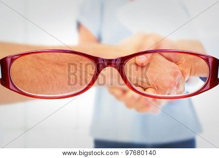 Casual businessmen shaking hands against glasses