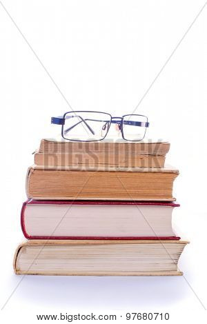Eyeglasses on a heap of books, isolated on white