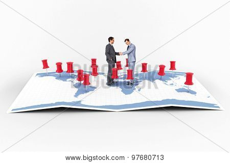 Businessmen shaking hands against world map with pointers