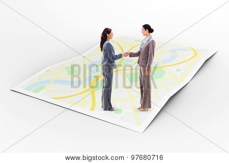 Two businesswomen shaking hands against city map