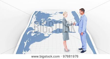Smiling business people shaking hands against world map
