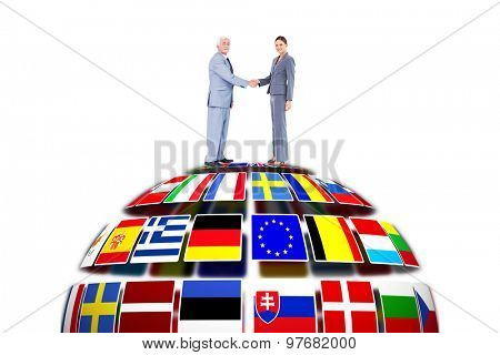Businessman and woman shaking hands against flag sphere