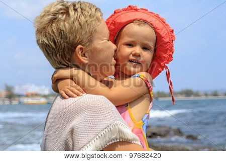 Young Mother Hugging Her Daughter On Beach