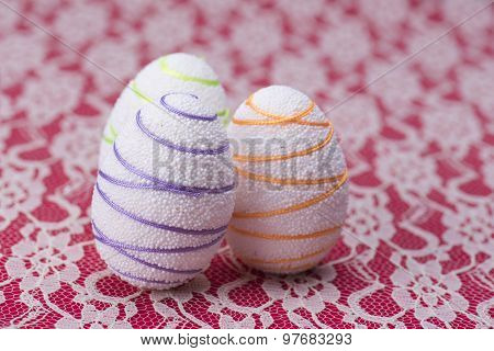 White Easter Eggs Against A Red And White Lacy