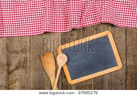 Chalkboard And Wooden Spoons With A Red Checkered Tablecloth
