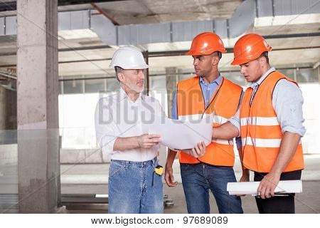 Cheerful builders are discussing a plan of construction
