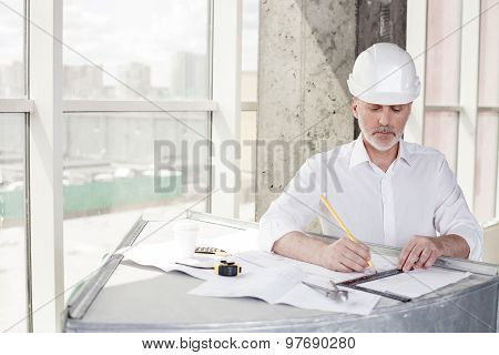 Successful old engineer is drawing sketches of building