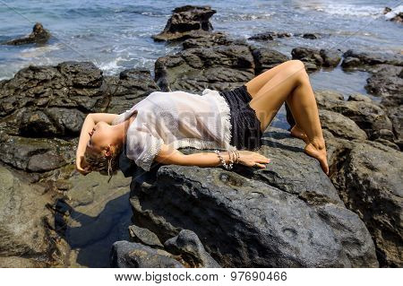Young Woman Relaxing And Meditating On Picturesque Rocky Seashore