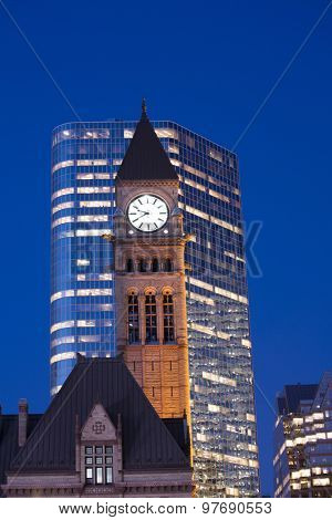 Detail of Toronto's city hall tower clock at dusk against modern building