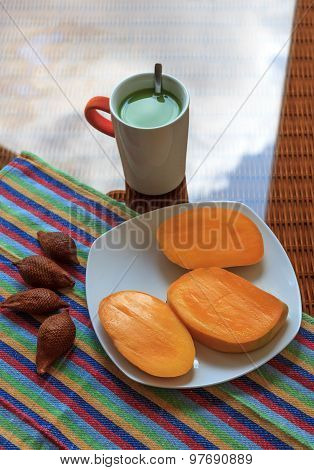 Cup Of Green Tea With Tropical Fruits On A Glass Surface
