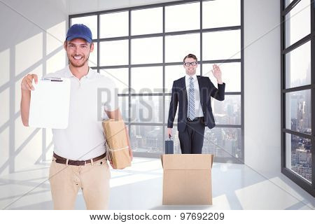 Happy delivery man holding cardboard box and clipboard against room with large window showing city