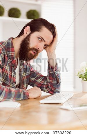 Hipster businessman stressed at his desk in his office