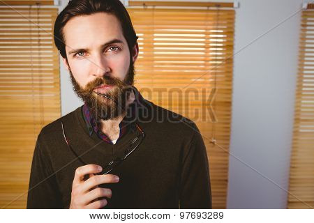 Hipster businessman frowning at camera in his office