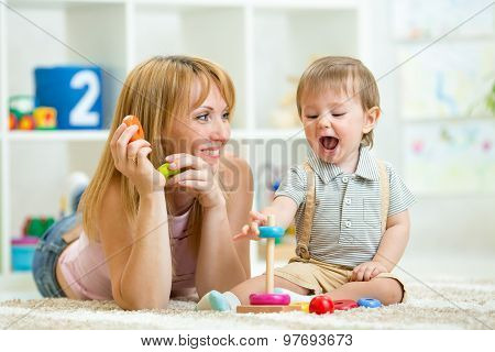 parent and baby boy playing together at home