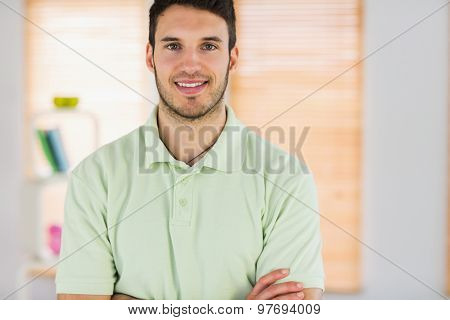 Portrait of smiling handsome masseur with arms crossed in a studio