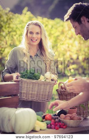 Portrait of a smiling blonde customer buying vegetables