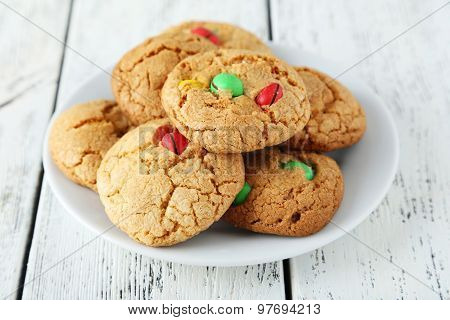 Cookies With Colorful Candy On Plate On White Wooden Background