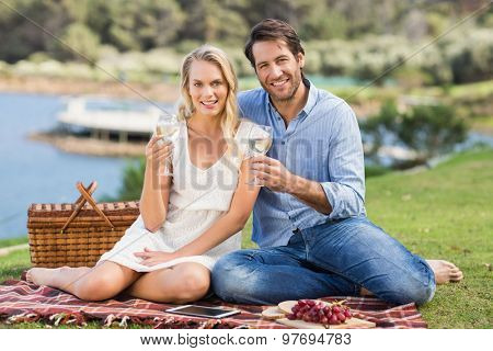 Portrait of a cute couple toasting with glass of white wine