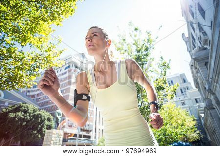 A pretty woman running in the street on a sunny day