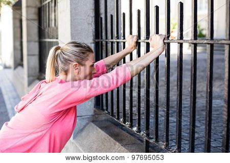 A beautiful woman stretching her body against a fence on a sunny day