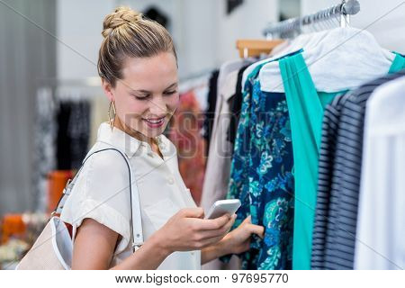 Smiling woman using smartphone while browsing clothes in clothing store