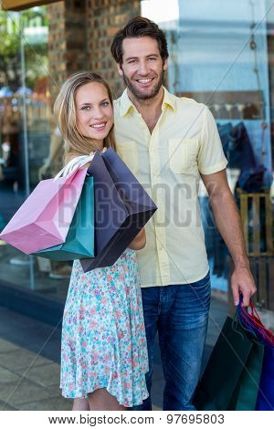 Portrait of smiling couple with shopping bags at shopping mall