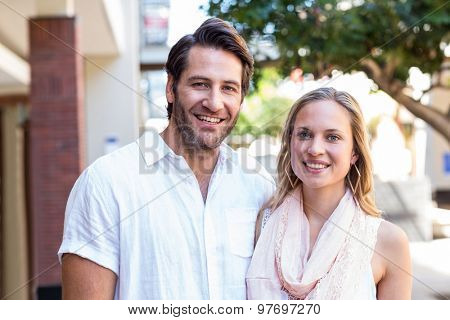 Portrait of smiling couple looking at camera at shopping mall