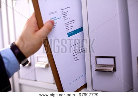 File folders, standing on  shelves in the background