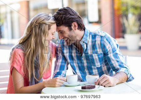 Cute couple sitting outside at a cafe head to head on a sunny day