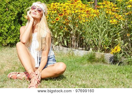 Beautiful smiling woman sitting on a grass outdoor.