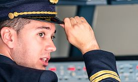 stock photo of cabin crew  - Young pilot first officer ready for takeoff in flight simulator school training - JPG