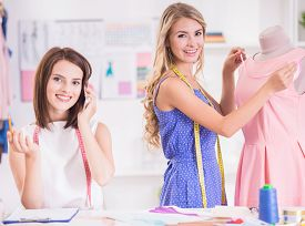 foto of dress mannequin  - Blond hair woman working at pink dress on mannequin and brown hair woman speaking by phone in studio - JPG