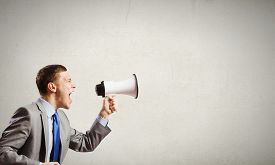 foto of screaming  - Young furious man screaming agressively in megaphone - JPG