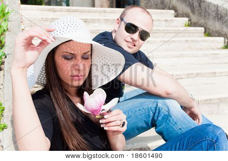 Young couple sitting on the stairs and discussed - girl holding flower