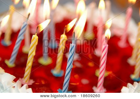 Celebratory cake and burning candles (shallow dof)