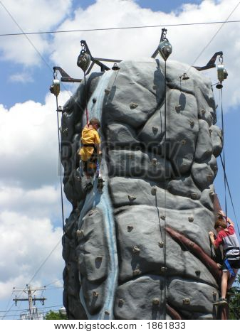 Two Boys On Rock Climbing Wall