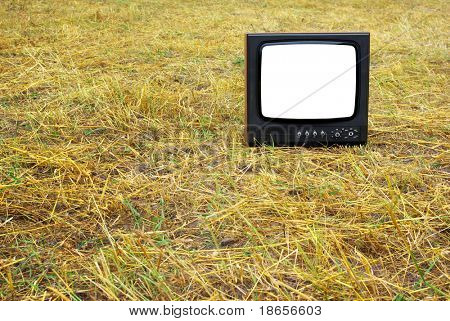Old television set stand on hay. Conceptual design.
