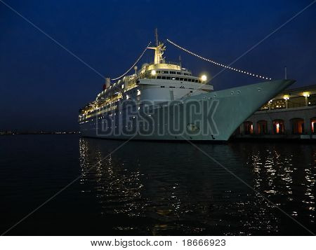 Old ocean liner at the shore blue tint, night view many lights