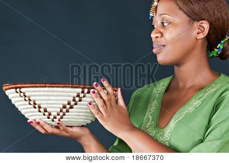 traditional african woman looking at  botswana basket, dark background