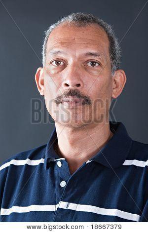 Retrato de un hombre cubano edad media sobre fondo oscuro
