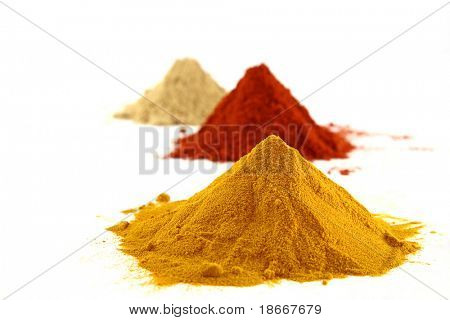a pile of ground turmeric on white background with paprika and ginger piles, bright colors.