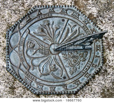 Ancient sundial in  a garden in old english castle without shadow; Cornwall; England.