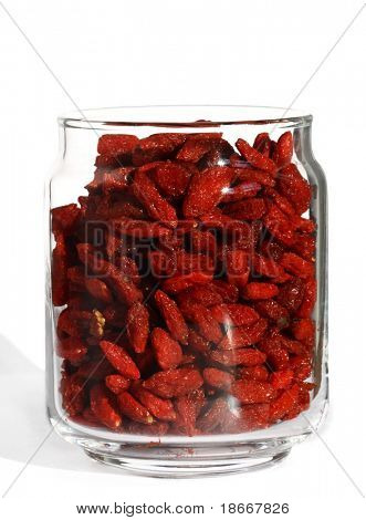 goji wolfberry in opened glass jar, bright color, white background and ligth shadow