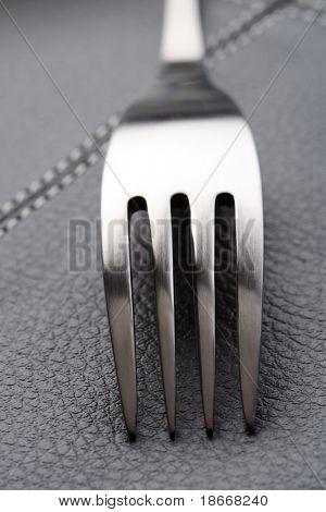 metal fork on black leather place mat, close-up shot