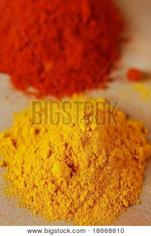 two color spices - pile of ground turmeric and paprika, shallow DOF, focus on top of the yellow pile.